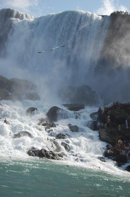 滝壺には風の洞窟観光する人々